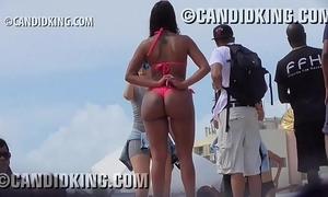 Tan latin babe with large wazoo pawg in a strap bikini on the beach!