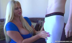 Huge-titted blond strokes a youthful guy's penis
